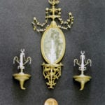 Detail view of a museum scale model of a tiny mirror and sconces created for the Rosalie Whyel Museum with a penny coin for scale