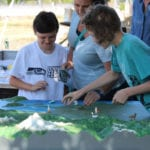 Visitors interacting with the Watershed topographic scale model